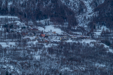 homes in the mountains surrounded by snow-covered trees and fresh snow