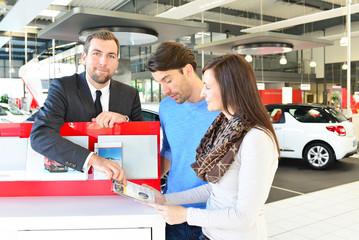 Verkauf von Fahrzeugen im Autohaus: Verkäufer berät junges Paar