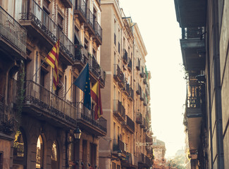 alley at barcelona with some spain and europe flags on building in warm sunlight