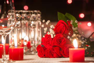Romantic date night. Red roses on a table surrounded by candle lights.