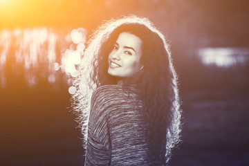 Smiling beautiful girl with curly, hair illuminated by the sun on a beautiful background of background of a summer sunset in black and white.