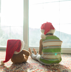 Christmas picture little boy in Santa hat with cute teddy bear s