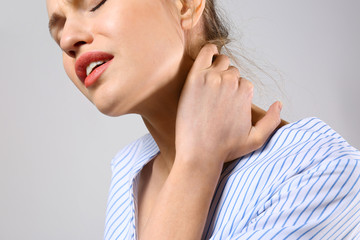 Young woman suffering from pain in neck on grey background