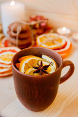 Tea with citrus in the ceramic brown cup. Dried citrus, cookies and candles on the background