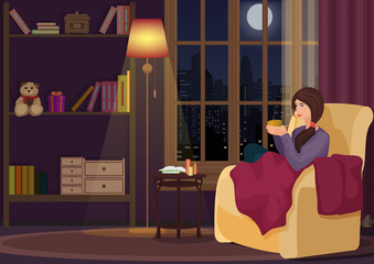 Young woman at home sitting in soft chear relaxing in her living room and drinking coffee or tea. Girl rests in night interior.