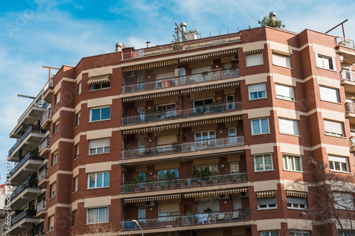 red brick apartment building with big balconies imagens