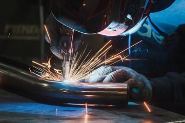 Welder in mask welding metal and sparks metal