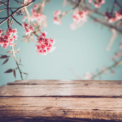 Wall Mural - Top of wood table with pink cherry blossom flower (sakura) on sky background in spring season - Empty ready for your product and food display or montage. vintage color tone.