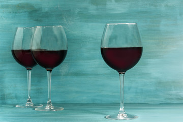Glasses of red wine on turquoise blue with copyspace