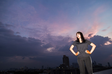 Sports young woman stand on top of building