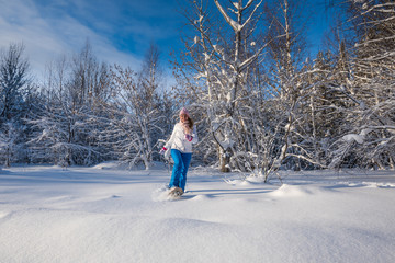 Winter sport activity. Woman with snowshoes on fluffy snow in forest. Beautiful landscape with coniferous trees and white snow.