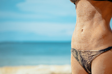 A girl with a beautiful slender figure against the sea. Close up of a slim woman abs covered in sand of a tropical ocean beach