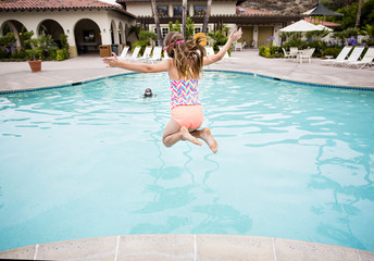 Child jumping into a big swimming pool