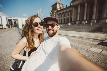 Happy couple taking selfie near Reichstag in Berlin. Funny students taking picture for travel blog in Germany.
