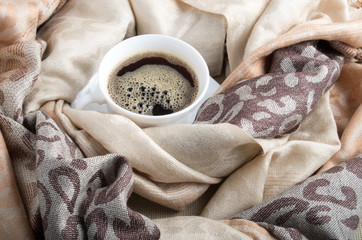 Cup of hot coffee in the folds of the female scarf