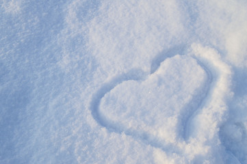 Heart symbol drawn on the pure white sparkling snow