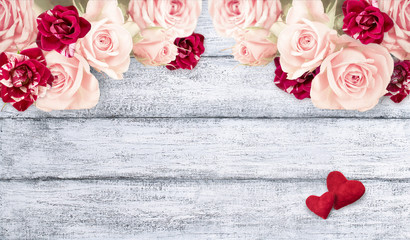 Roses with two hearts on background of shabby wooden planks.