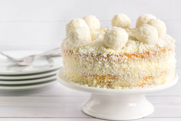 Whole coconut cake with coconut balls on top, white background. Plates and forks for serving in the background.