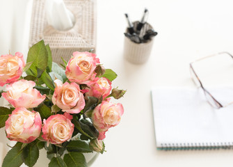 High angle view of pink and cream roses in glass vase on white desk with tissues, pens notebook and glasses (selective focus)