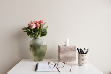 White desk against wall with pink and cream roses, tissue box, pens, notebook and glasses (selective focus)