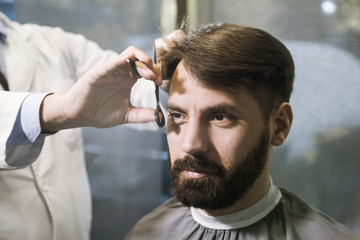 Front view of a bearded businessman having his hair cut in a barber shop. Concept of being well groomed