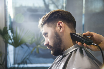 Close up of barber's hands trimming a serious businessman's hair. Concept of looks importance for good impression