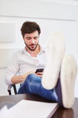 Junger Mann liest SMS auf dem Smartphone