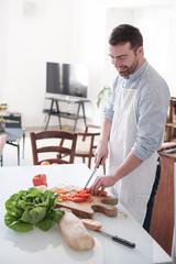 Man cooking at home and preparing food