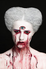 Mysterious beauty portrait of snow queen covered with blood. Bright luxury makeup. Gore dripping from the mouth.