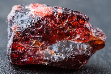 Uncut and rough deep red rhodolite garnet gemstone.