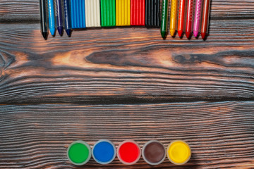 wax crayons, finger paints and plasticine, copyspace, rustic wooden background