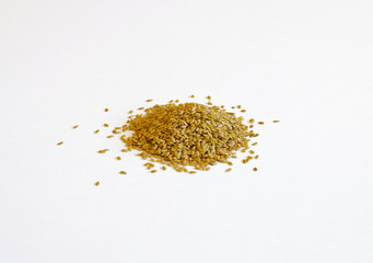 Pile of golden flax seeds on a white background