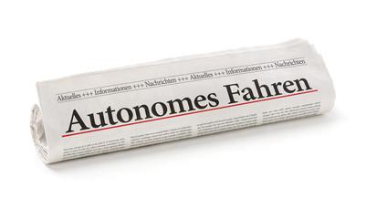 Zeitungsrolle mit der Überschrift Autonomes Fahren