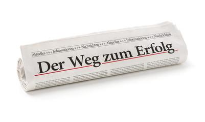Zeitungsrolle mit der Überschrift Der Weg zum Erfolg