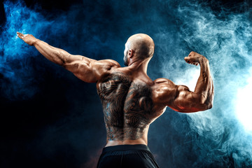 Bald unrecognizable tattooed man with strong muscles posing with arm up in smoke.