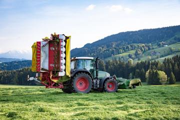 Grasernte im Allgäu, Traktor mit angehobenem Mähwerk