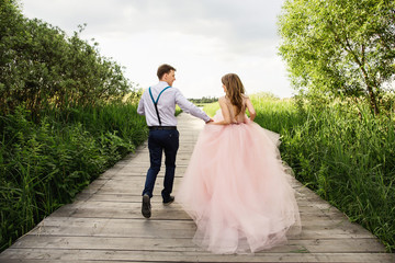 Wedding couple, happy bride and groom running on wooden bridge to place of wedding ceremony. Wedding concept