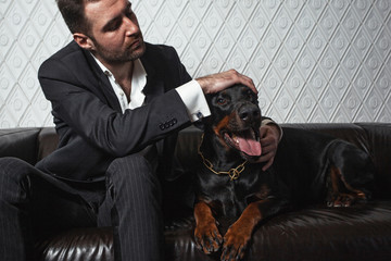 The man in a business suit. Holds hand on Dobermann terrier