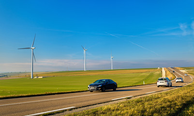 Cars on a highway and wind turbines in the background - France