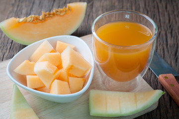 Kitchen table with Glass of cantaloupe melon juice on cutting board. healthy eating and dieting food, concept of health care, Image focus top view.