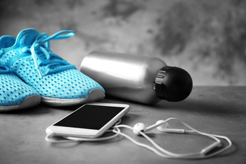Sport shoes, bottle of water and smartphone with earphones on grey table closeup