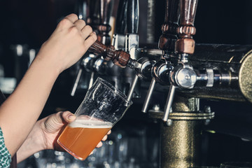 Woman pouring cold beer into glass in bar, closeup