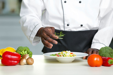 African American chef cooking tasty salad in kitchen, closeup