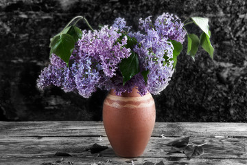 bouquet of lilac in a vase on the background of wooden walls dark colours