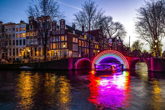 AMSTERDAM, NETHERLANDS - JANUARY 10, 2017: Cruise boats rush in night canals. Light installations on night canals of Amsterdam within Light Festival. January 10, 2017 in Amsterdam - Netherland.