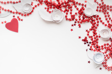 red beads, red heart,  red star and white paper flower on a whit