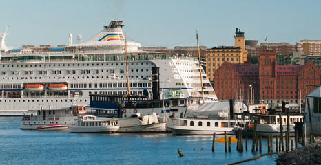 Cruise ship and small boats in the bay against the backdrop of the city's buildings.