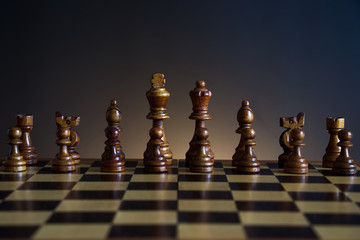 chessboard with black wooden figures, chess with a dark color gradient background