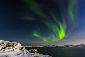 A cozy house on the coast of the Barents Sea and the aurora. Kola Peninsula, Murmansk region