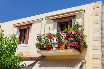 A balcony  with lot of pots with flowers in the second part of  old house located in  Old Town of Rethymnon